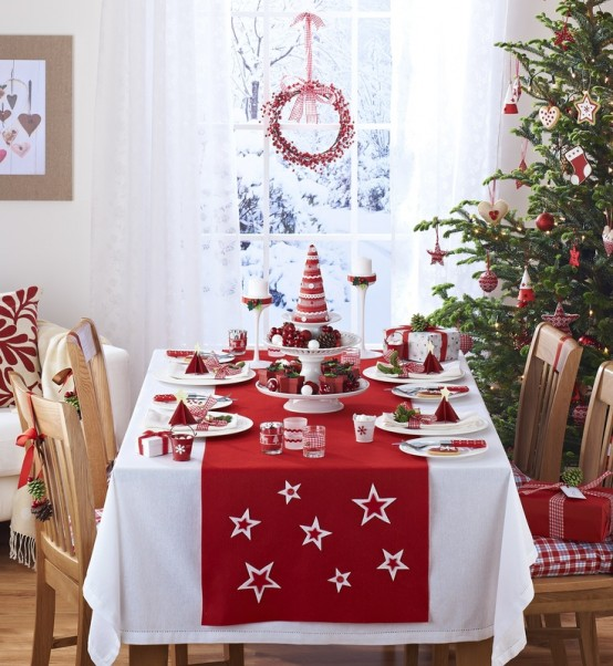 a Christmas tree with red and white ornaments, red and white runner, napkins and candles for a holiday feel
