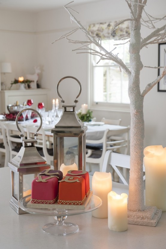 a frozen white Christmas tree, candles, candle lanterns and red touches for a holiday feel