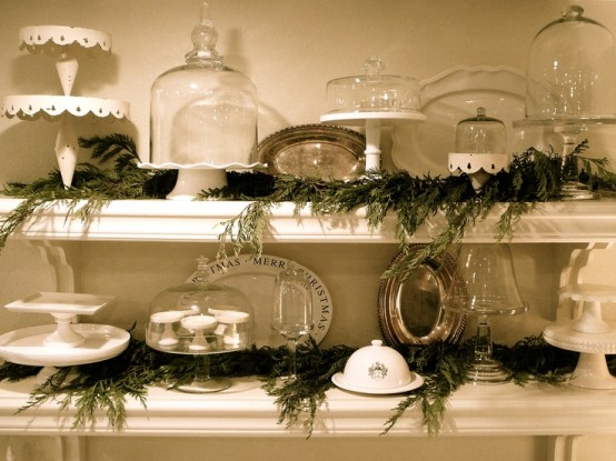 evergreen garlands placed right on the shelves add a rustic and natural feel to the kitchen