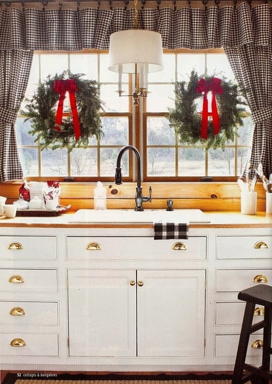 a buffalo check curtain and towel, evergreen wreaths with red bows bring a Christmas feel to the space