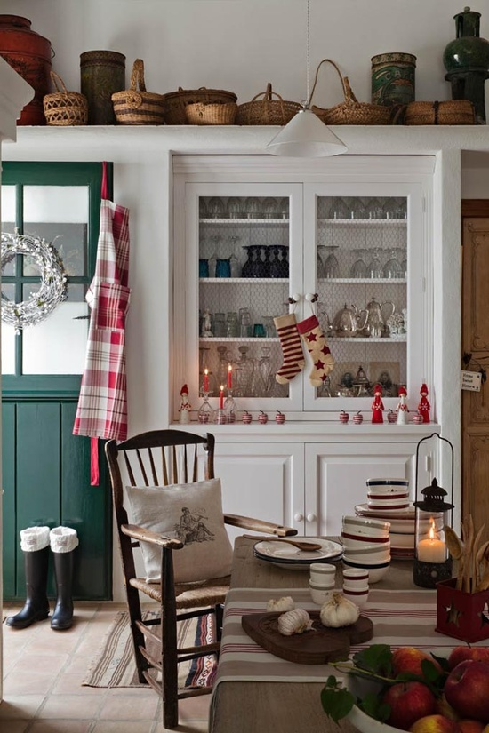 a plaid apron, red and white candles and accessories and printed stockings for a cozy holiday feel in the space