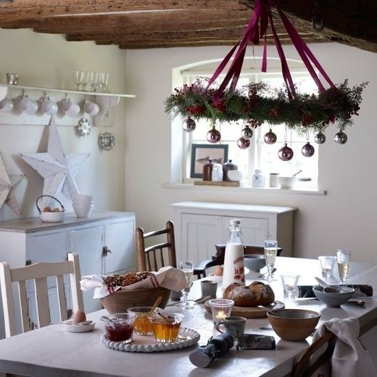 a Christmas chandelier with evergreens, purple ribbons and pastel ornaments over the table and a large white star