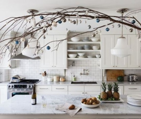 branches with white and blue ornaments over the kitchen island make the space feel holiday-like