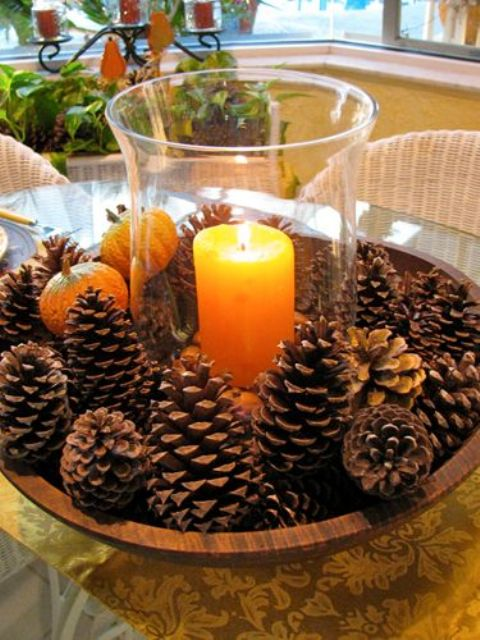a simple and eays to make fall centerpiece of a wooden bowl with pinecones, faux pumpkins and a candle in a clear candle holder