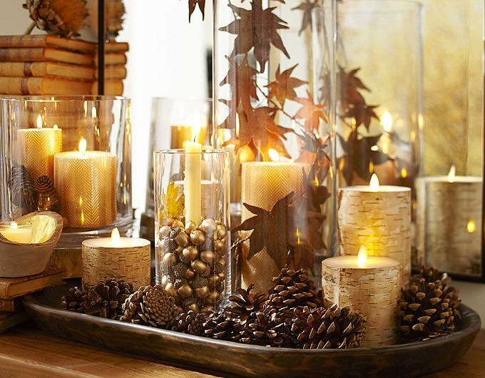 a simple and stylish centerpiece of a tray with pinecones, gilded candles, fall leaves and little acorns
