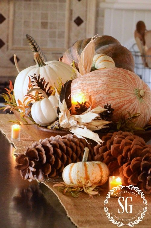 a lush fall centerpiece of oversized pinecones and pumpkins, fall leaves and corn husks plus candles is ideal for a Thanksgiving party