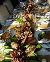 a Thanksgiving table runner of feathers, foliage and large pinecones is a chic rustic idea
