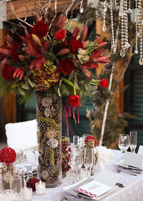 a refined Thanksgiving centerpiece of a tall vase filled with moss and pinecones and bold burgundy blooms and greenery