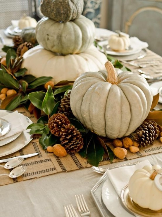 a stylish Thanksgiving centerpiece of pinecones, nuts, foliage and oversized neutral pumpkins stacked