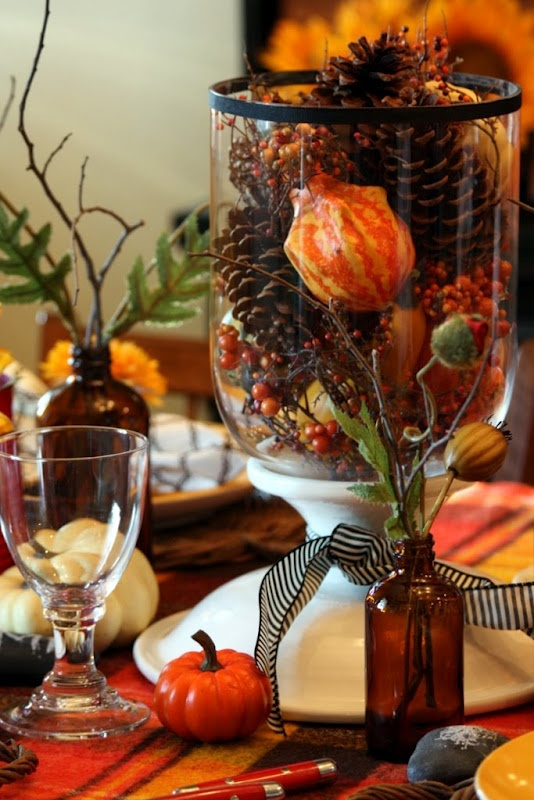 a simple fall centerpiece of a tall clear vase filled with fake berries, pinecones and gourds