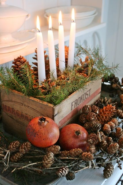a rustic centerpiece of a crate with evergreens and pinecones plus candles and pinecones and pomegranates around