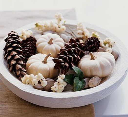 a chic neutral fall centerpiece of a white bowl filled with pinecones, white pumpkins, pebbles and white berries