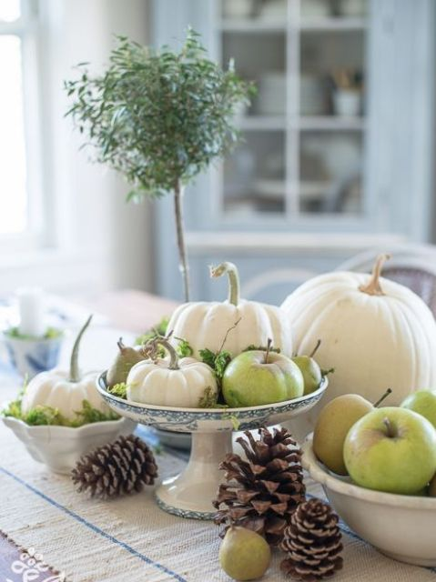 a cute fall centerpiece of a porcelain stand with foliage, pumpkins, apples and pears for a harvest touch