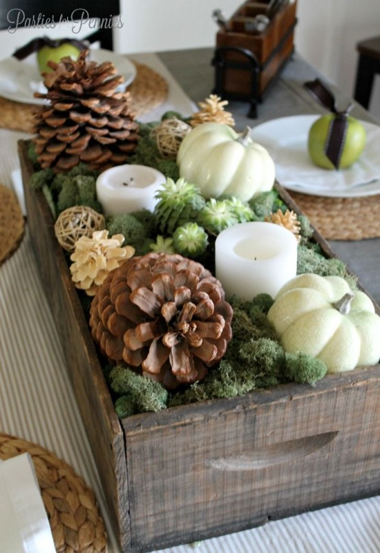 a gorgeous fall centerpiece of a crate with moss, succulents, candles, usual and bleached pinecones and pumpkins