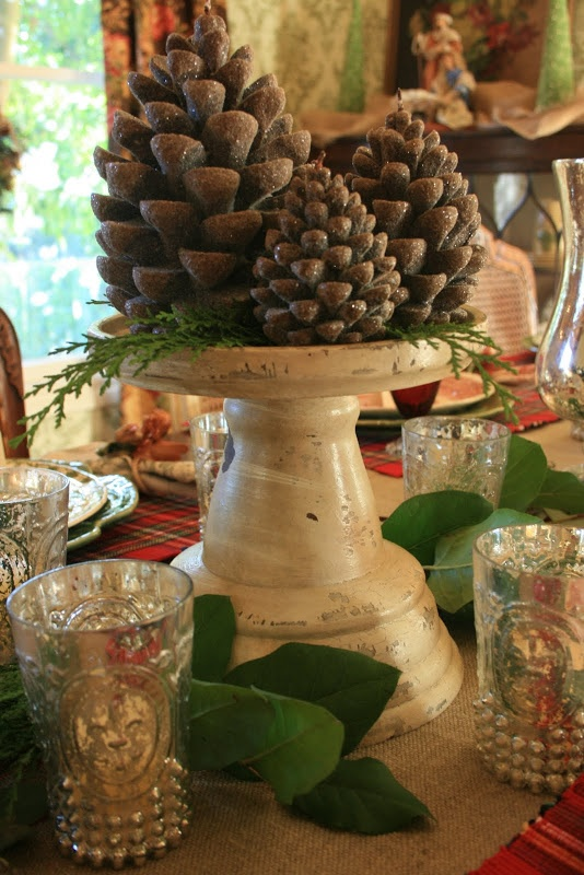 a vintage meets rustic centerpiece of a vintage stand and oversized glitter pinecones for a cool fall look