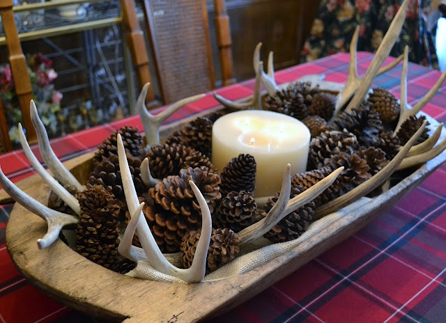 a rustic fall centerpiece of a dough bowl with pinecones, antlers and a large candle in the center
