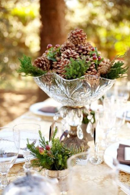 a crystal bowl and evergreens plus pinecones and berries for a vintage and rustic touch