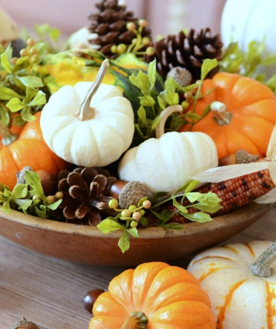 a stylish harvest-inspired centerpiece of a wooden bowl, foliage, corns and acorns,pinecones and various pumpkins