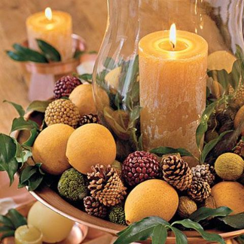 a chic Thanksgivign party centerpiece of a metal tray filled with pinecones, fruits, pea balls and foliage plus a large candle in the center