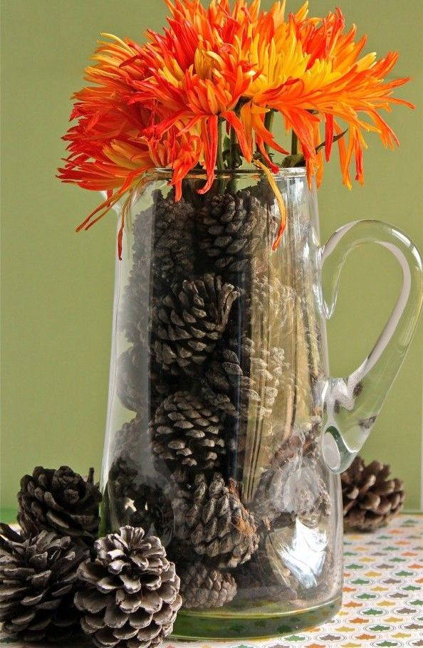 a simple clear glass jug filled with pinecones and topped with bright fiery red blooms for a fall inspired space