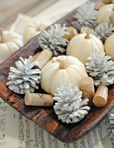 a quirky fall centerpiece of a wooden bowl, white pumpkins, whitewashed pinecones and wine corks