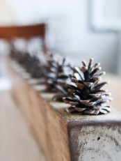 a rough rustic centerpiece made of a wooden slab and pinecones inserted into it for a cozy feel