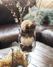 a casual clear vase centerpiece of pinecones, white pumpkins and blooming branches for the fall