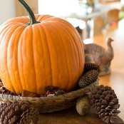 a bold fall centerpiece of a wicker bowl with pinecones and a large orange pumpkin will bring a rustic feel to the space