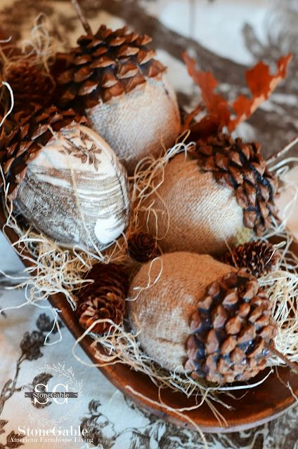 a whimsy wedding centerpiece of a wooden bowl with hay and pinecones made of burlap and usual pinecone parts