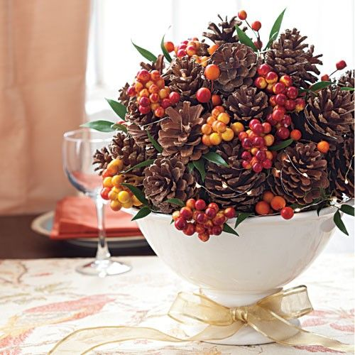 a luxurious Thanksgiving centerpiece of a white bowl with pinecones, berries, foliage and with a playful gold bow