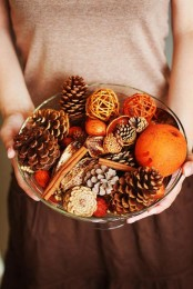 a glass bowl with pinecones, nuts, acorns, cinnamon sticks and colorful yarn balls