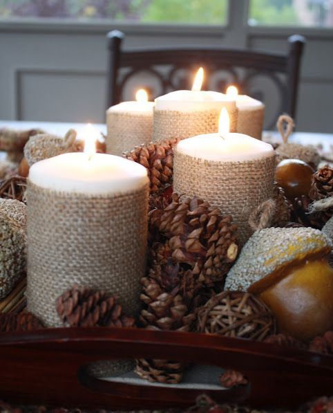 a stylish centerpiece of a tray with pinecones, faux acorns and candle wrapped with burlap