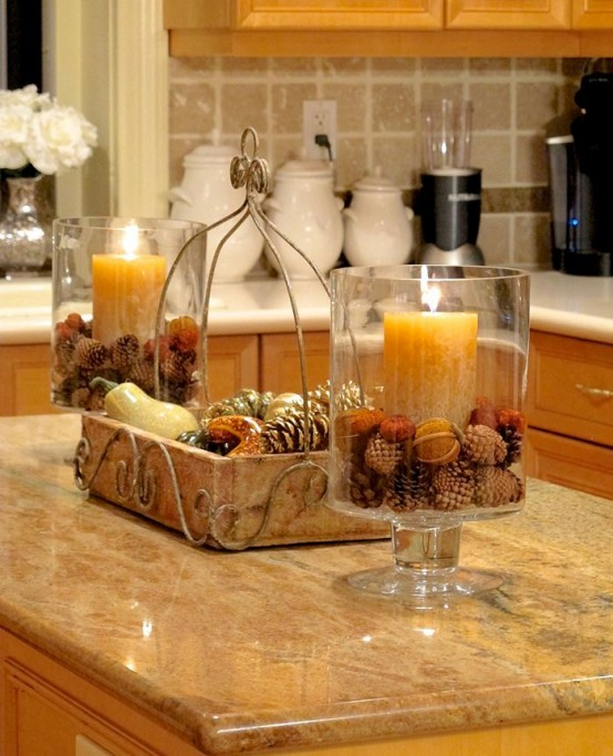 a casual fall centerpiece of a wooden tray filled with pinecones and bulbs, with vases with pinecones and nuts plus candles next to it