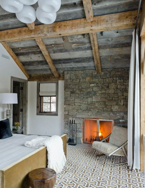 Simple furniture and textiles can balance out a texture heave interior that features such things as a weathered wooden ceiling and a stone fireplace.