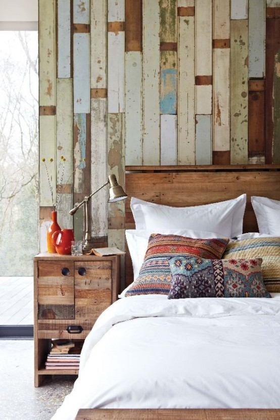 An accent wall covered with rough wood planks that show their paining history is a perfect addition to a rustic bedroom.