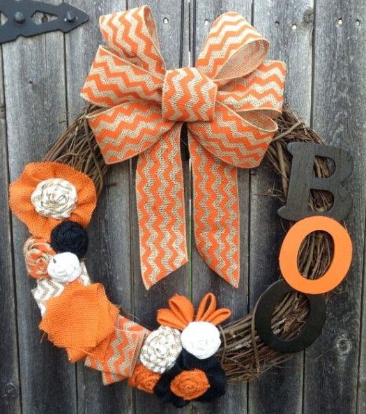 a rustic Halloween wreath of vine, with a printed orange bow, letters, fabric blooms and bows is bright and fun