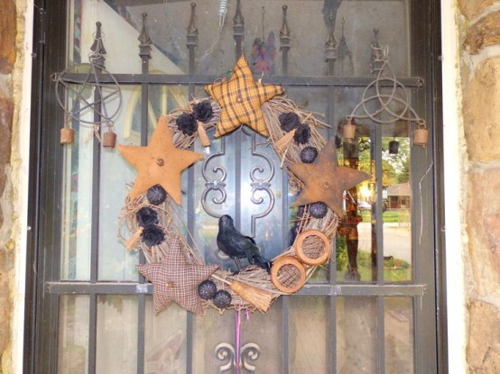 a vintage rustic Halloween wreath of vine, with fabric stars, nuts, pinecones and a crow is a bold and scary decor idea