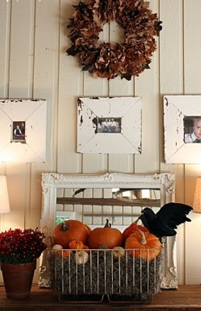 a dried leaf and dark bloom wreath, a wire basket with hay, pumpkins and a crow for styling your space for Halloween