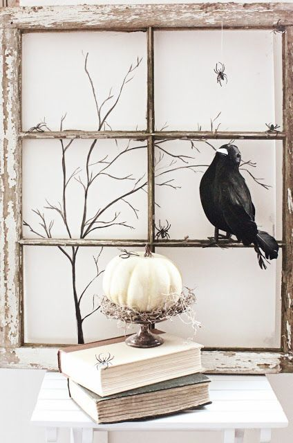 a shabby chic window frame, a crow, branches and a pumpkin on a stand with hay is stylish for a rustic Halloween space