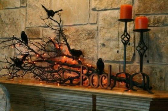 rustic Halloween mantel styling with scary branches, blackbirds, candles and lights and orange candles is very chic