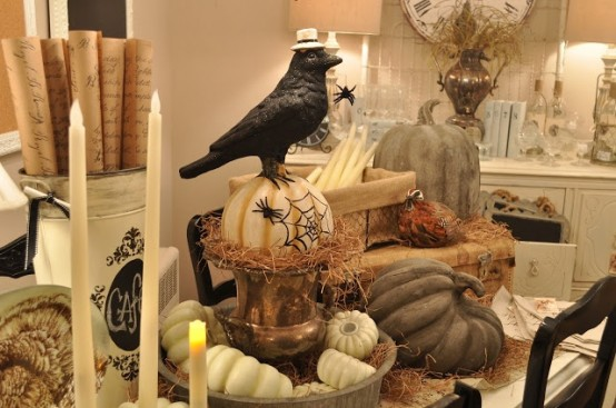 rustic Halloween table styling with candles, pumpkins, a crow on top a pumpkin, spiders and hay is chic and not very scary