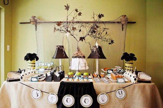 a dessert table with a burlap tablecloth, rustic vintage table lamp, dried leaves and blooms and dark blooms