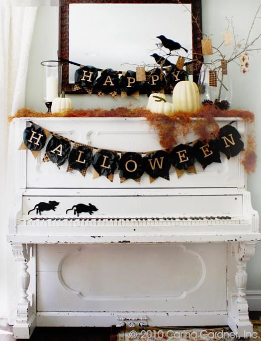 rustic Halloween decor with burlap and black fabric banners, orange hay, crows, branches and white pumpkins