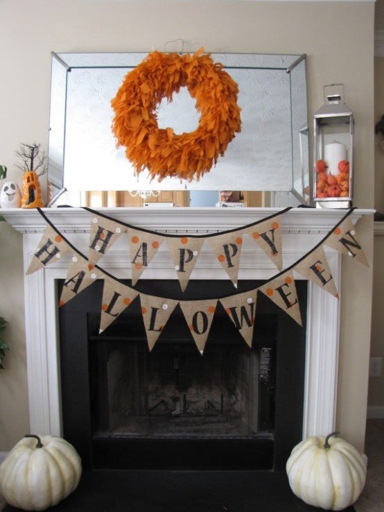 an orange feather wreath, a burlap banner and pumpkins for simple rustic Halloween decor