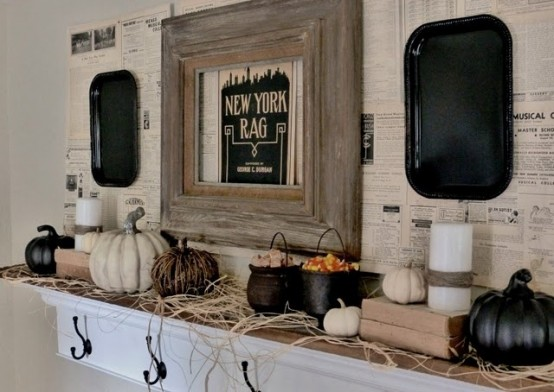 a rustic Halloween mantel with hay, black and white pumpkins, candles, cauldrons with candies and black trays