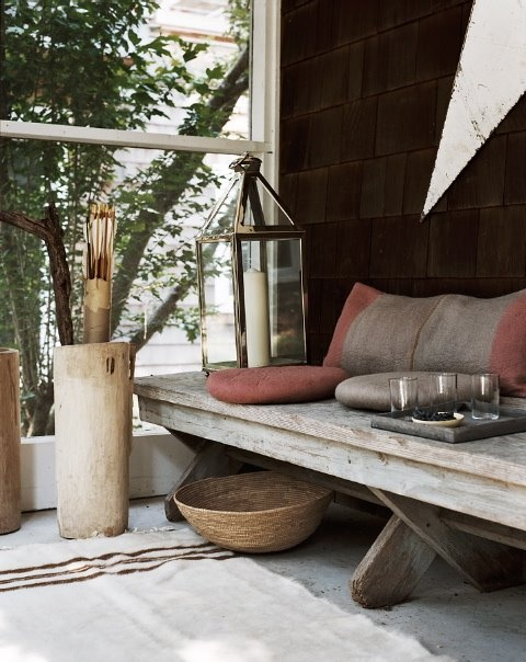 a rustic space with a wooden bench, with a basket, a candle lantern and a concrete container