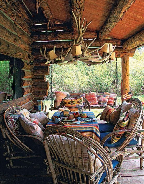 a rustic meets boho patio with rattan and wooden furniture, colorful textiles and an antler chandelier