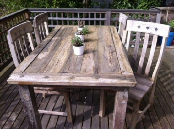 a simple rustic dining space wirh a wooden dining set and some potted plants