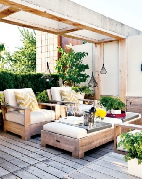 a welcoming and bright rustic meets contemporary patio with upholstered furniture, candle lanterns and greenery and bright touches
