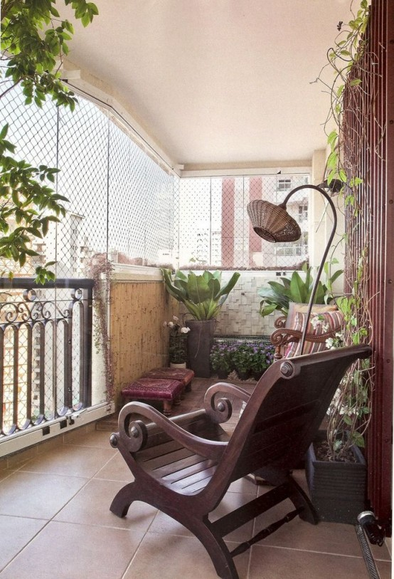 a rustic meets boho balcony with dark stained furniture, a wicker floor lamp and much greenery